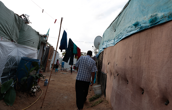 """A community leader makes his way to the tent of a pregnant 14-year-old former child bride. """"I am worried about the delivery,"""" said the girl's father. © UNFPA/David Brunetti"""