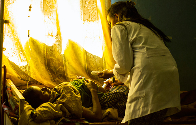 Fasika Maru, a midwife, examines Anguach Abebaw at the Ambesame Health Centre. Ms. Anguach is in labour, but her foetus is in a dangerous position. © UNFPA/Mulugeta Ayene