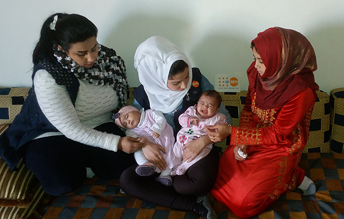 Fatima and Rasha are visited by a UNFPA coordinator after the birth of their daughters. The babies were born on the same day. © UNFPA Syria