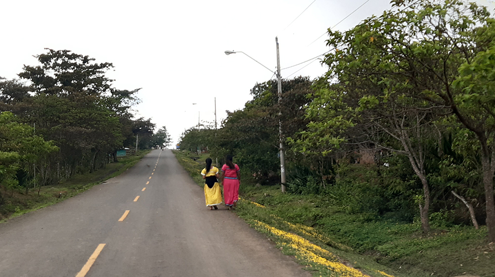 Two women walk along a paved road. For some communities, the nearest health centre is two days away. ©UNFPA Panama/Osman Esquivel López