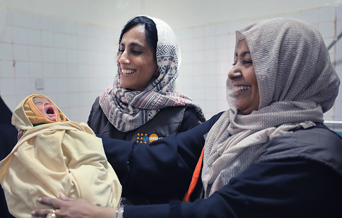 UNFPA's former representative in Yemen, Anjali Sen, and reproductive health expert Afrah hold a newborn baby. UNFPA is the sole provider of life-saving reproductive health supplies and medicines in Yemen. © UNFPA Yemen