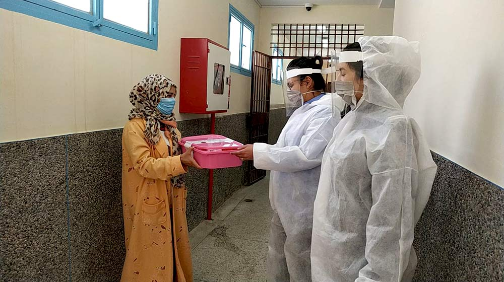 Health personnel in personal protective equipment accept a SALAMA kit, a pink plastic tub containing COVID-19 prevention supplies.