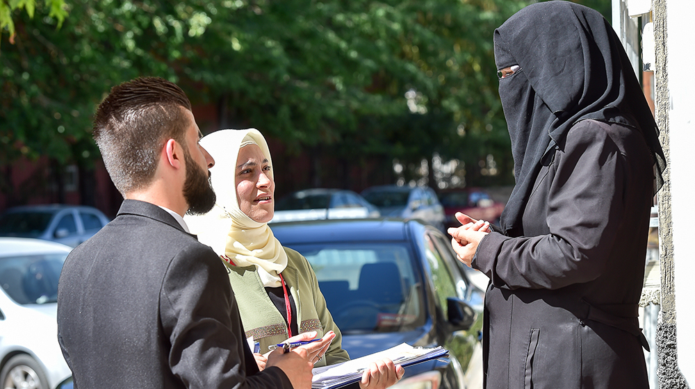 Two outreach workers, a man and a woman, speak to a woman in a refugee community in Turkey.