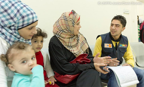 Health Worker at UNFPA-supported clinic talks to family