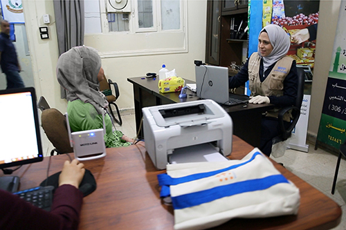 A Syrian woman speaks with an aid worker sitting at a computer.