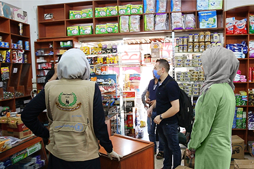Syrians and aid workers speak in a store stocked with food and hygiene supplies.