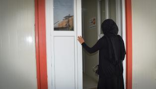 A woman stands in the doorway of the Women and Girls' Treatment and Support Centre in Dohuk, Iraq.