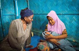 Dr. Natalia Kanem sits to the left of a new mother holding her infant baby in Kutupalong settlement, Bangladesh.