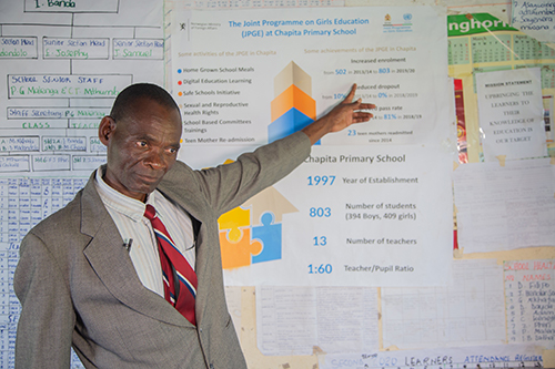 Mr. Zatha points to a poster showing some of the results of the programme in Chapita Primary School.