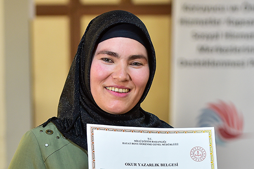 Salimeh smiles widely as she holds her literacy certificate.